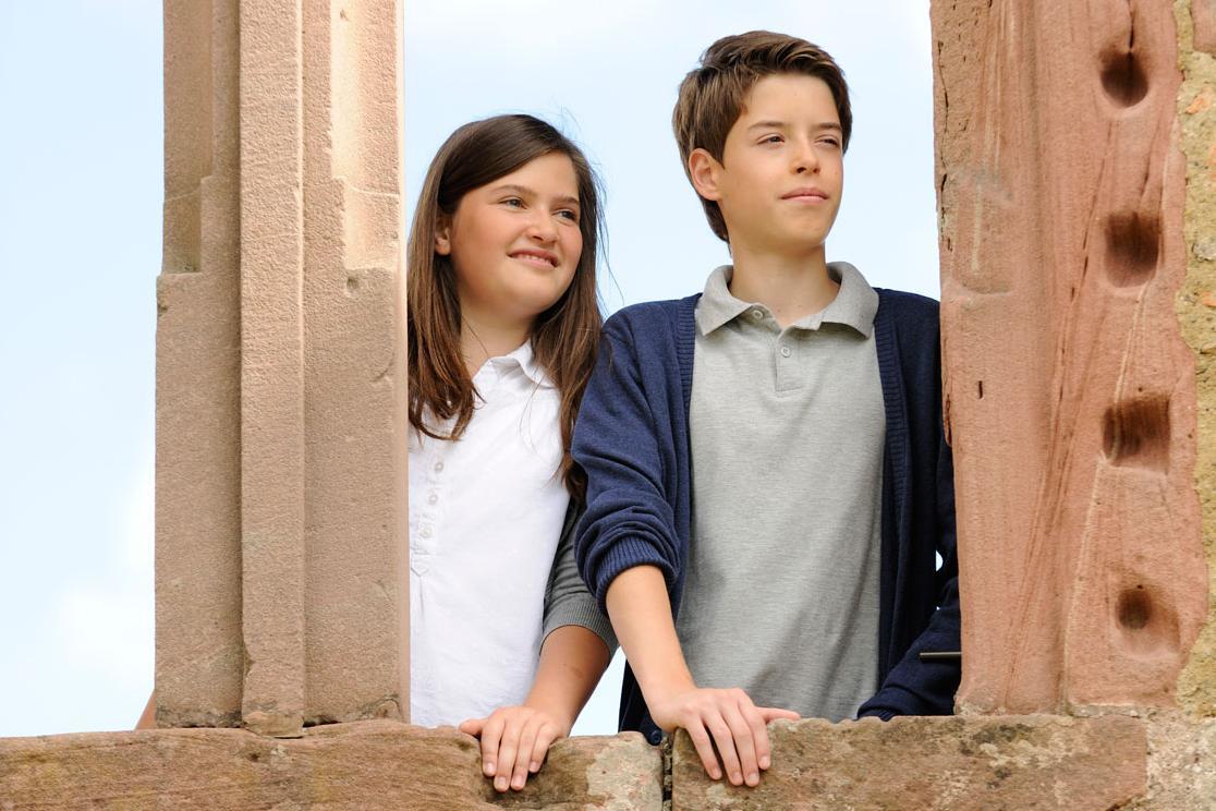 Mädchen und Junge an einem Burgfenster