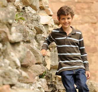 Junge auf einer Burgmauer; Foto: Staatliche Schlösser und Gärten Baden-Württemberg, Niels Schubert